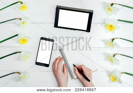 Top View On Table With Narcissus, Empty Diary, Tablet, Phone And Girl's Hands With Pen, Free Space.