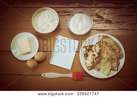 Eggs, Butter, Flour, Sugar, Baked Pancakes And Notebook On Rustic Wooden Background