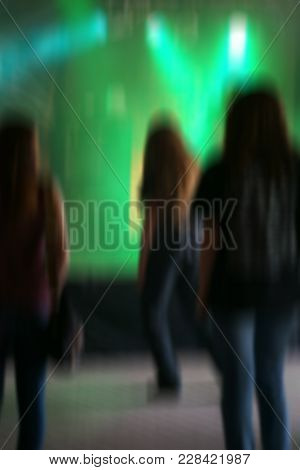 Blurred Spectators In Front Of A Colorful Illuminated Stage At A Heavy Metal Concert.