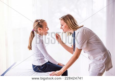 Young Female Doctor Examiming A Small Girl In Her Office.