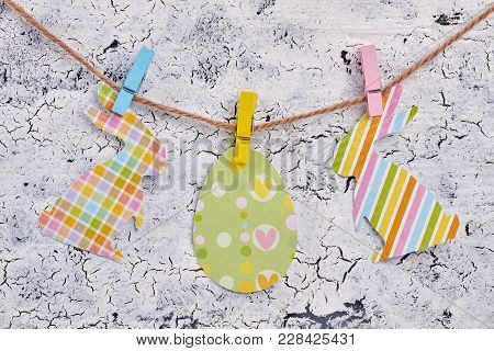 Paper Patterned Cutouts On Rope. Papercut Egg And Rabbits Hanging On Clothesline With Clothespins On