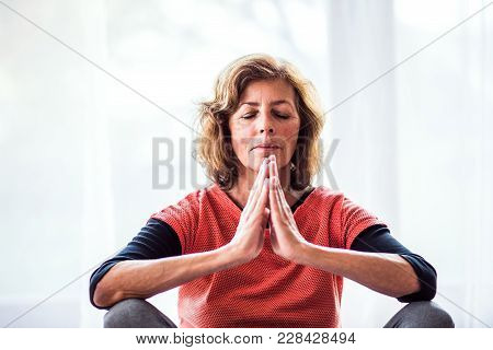 Active Senior Woman Meditating At Home, Eyes Closed.