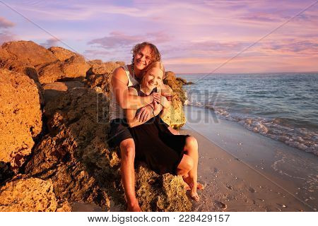 A Happy Young Married Couple Is Smiling As They Sit With Their Arms Around Eachother On A Rocky Beac