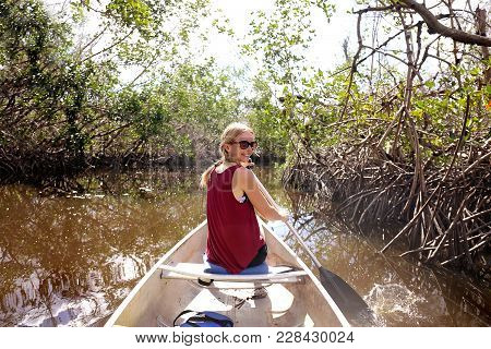 A Happy Young Woman Is Smiling As She Paddles A Canoe Through The Mangrove Forest In A River In The