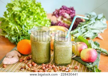 Two Glass Jars Of Green Smoothie Surrounded By Fresh Fruit And Green Leafy Vegetables.