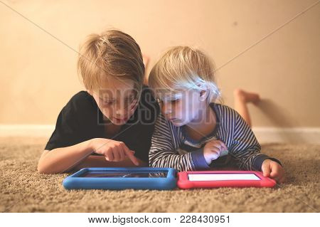 An 8 Year Old Big Brother Is Showing Is Little Sister How To Play A Game On Their Electronic Tablets
