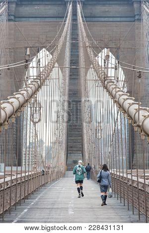 Runner Running Across Brooklyn Bridge. New York City Manhattan Downtown Skyline In Sunset With Skysc