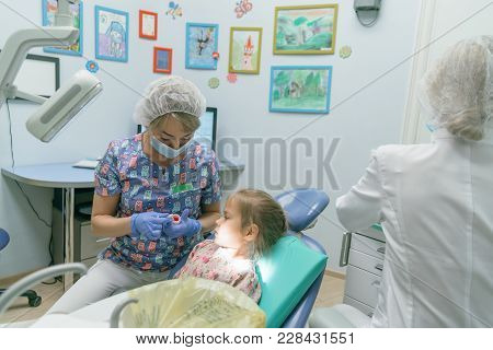 Child With A Mother At A Dentist's Reception. The Girl Lies In The Chair, Behind Her Mother. The Doc