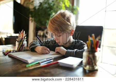 An 8 Year Old School Aged Child Is Working On A Coloring Art Project, Using Colored Pencils To Draw