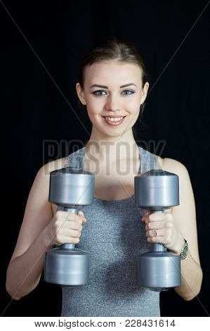 The Athlete Is Engaged With Heavy Dumbbells On A Black Background.