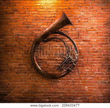 Old French Horn On Brick Wall Background.