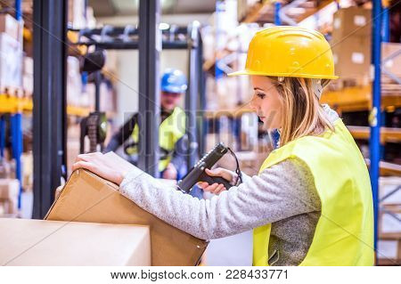Unrecognizable Warehouse Woman Worker Or Supervisor With Barcode Scanner. A Mobile Handheld Pc With