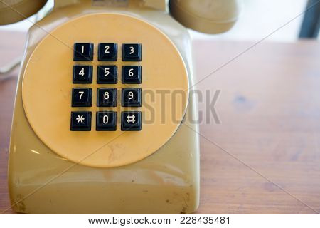 Old Yellow Telephone With Black Key Pad On Table