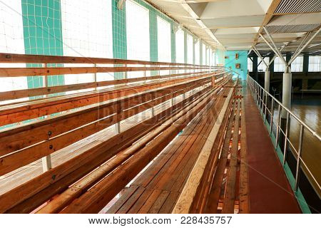 Rows Of Empty Wooden Benches In Sporting Hall. Tribune In Gym For Fans Of Matches With Empty Wooden