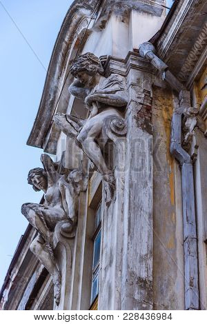 Two Statues Of Concrete Adorn The Facade Of An Old House