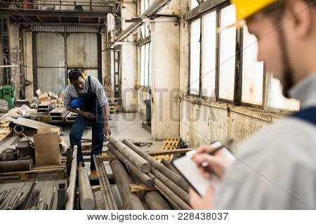 Multi-ethnic Group Of Workers Wearing Overalls Taking Inventory While Standing At Spacious Productio