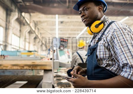 Concentrated African American Worker Wearing Overall And Hardhat Operating Machine With Help Of Digi