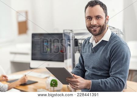 New Information. Joyful Bristled Young Man Leaning On The Desk In The Office And Posing For The Came