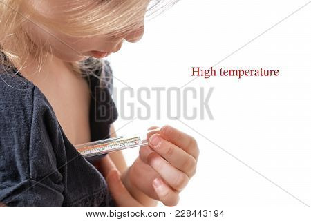 The Little Girl Measures The Temperature. Mercury Thermometer. Close Up. Looks At The Thermometer As