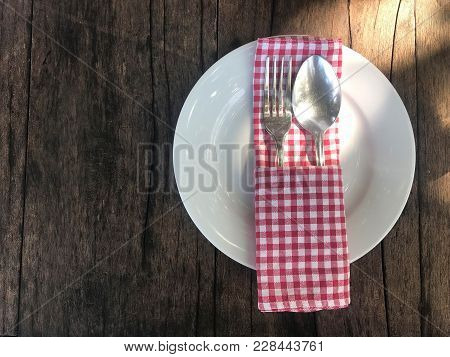 Empty White Plate With Silverware, Spoon And Fork And Red Scoth Napkin On Wooden Table With Copy Spa