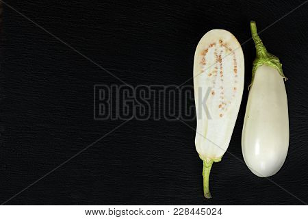 White Slice Eggplant On Black Stone Surface. Top View, Copy Space.
