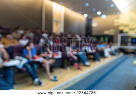 Abstract Blurred Photo Of Conference Hall Or Seminar Room With Attendee Background