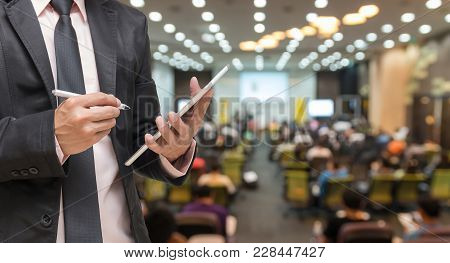 Businessman Using The Tablet On The Abstract Blurred Photo Of Conference Hall Or Seminar Room With A