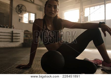 Fit Young Woman Sitting On Gym Floor With Medicine Ball. Females Resting After Training Session In H