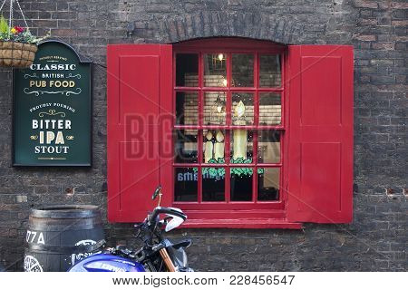 London, England - December 18 , 2017 Red Shutters And A Pub Window Decorated Before Christmas. Class