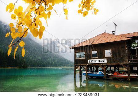Dobbiaco, Italy - 03 October, 2017: Dobbiaco Lake Or Toblacher In Dolomites With Wooden Boathouse Re