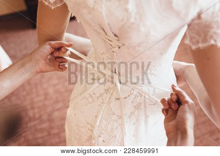 A Girlfriend Helps The Bride To Lace Her Wedding Dress
