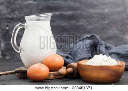 Preparation For Baking: Jar Milk, Egg, Rolling Pin, Flour In Bowl, Spoon, Kitchen Textile With Woode