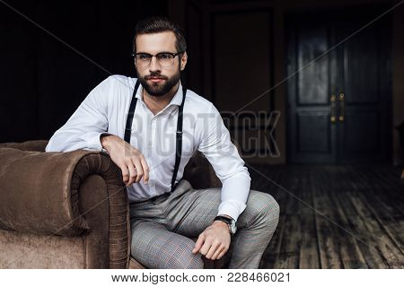 Fashionable Bearded Man In Glasses And Suspenders Sitting In Armchair