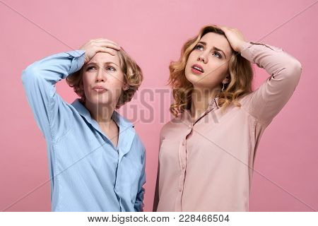 Two Attractive Women Hold Onto Their Heads With A Frustrated Expression On Their Faces. Loss And Fai