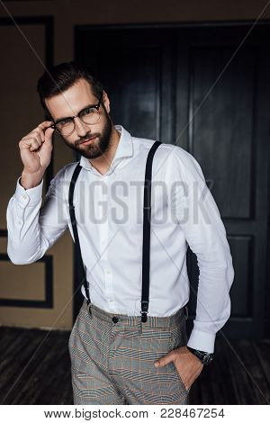 Fashionable Man Posing In Glasses, White Shirt And Suspenders