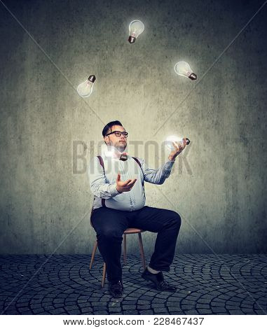 Young Chubby Man Sitting On Chair And Juggling With Light Bulbs Being Genius.