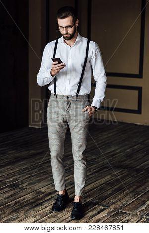 Stylish Bearded Man In Suspenders Using Smartphone In Loft Interior