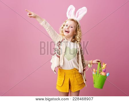 Festive Bunny And Eggs Season. Happy Trendy Child In Easter Bunny Ears Isolated On Pink Pointing At
