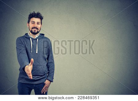 Smiling Hipster Man Outstretching Hand For Shake In Gesture For Agreement.