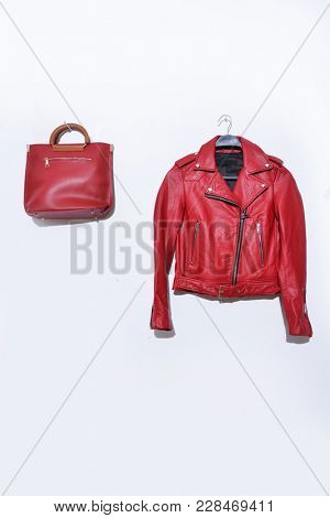 Leather red jacket with handbag isolated on hanging