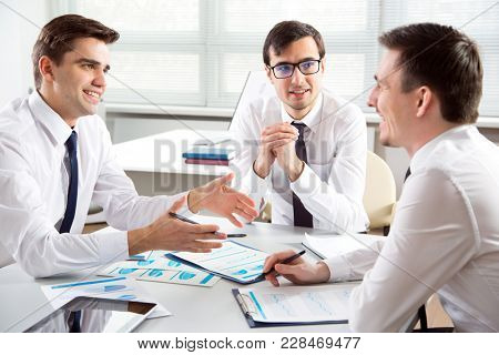 Three businessmen working together on a new project in the office