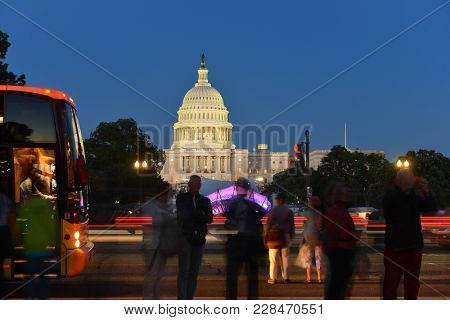 Tourists and a tour bus in front of the US Capitol Building at night - Washington DC, United States