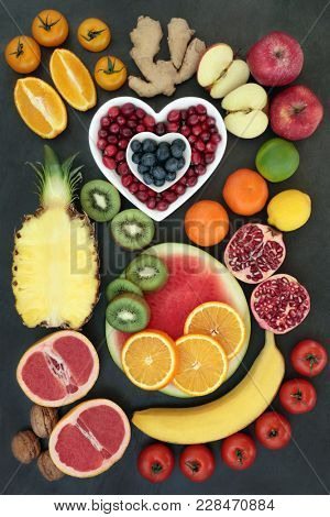 Super food for healthy eating with fresh fruit, vegetables, nuts and spice high in antioxidants, anthocyanins, fibre, vitamins and minerals. On slate top view.
