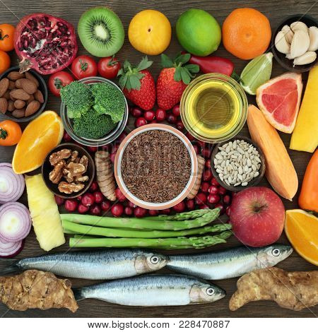 Super food for a healthy lifestyle concept with foods high in omega 3, antioxidants, anthocyanins and vitamins with fresh sardines, fruit, vegetables, seeds, nuts, herbs, spice and olive oil.