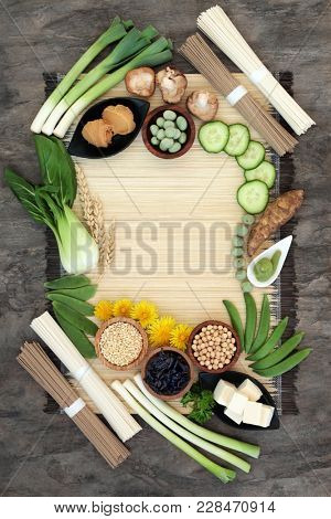 Macrobiotic diet food background with tofu, udon and sobu noodles, miso paste, grains, legumes, vegetables and wasbai nuts with foods high in protein, antioxidants, fibre, vitamins and minerals.