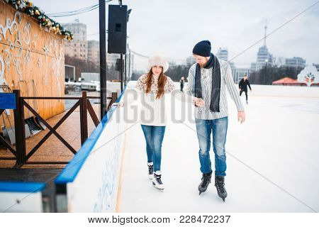 Love couple, man learn woman to skate on the rink