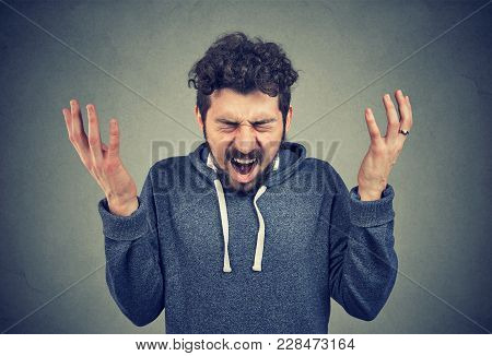 Casual Young Hipster Man Shouting With Eyes Closed Suffering From Stress And Pressure.