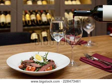 Pouring red wine in a glass, gourmet restaurant