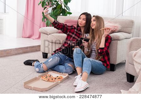 Time To Have Fun! Nice Looking Delightful Beauties Making Pictures Of Themselves While Sitting On Th