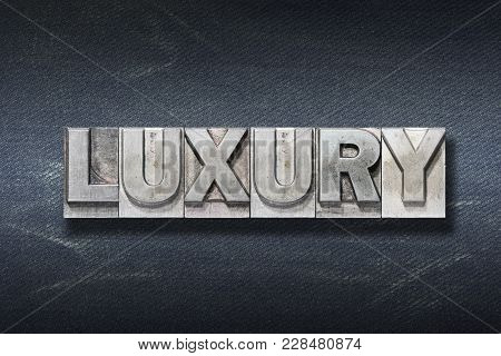 Luxury Word Made From Metallic Letterpress On Dark Jeans Background